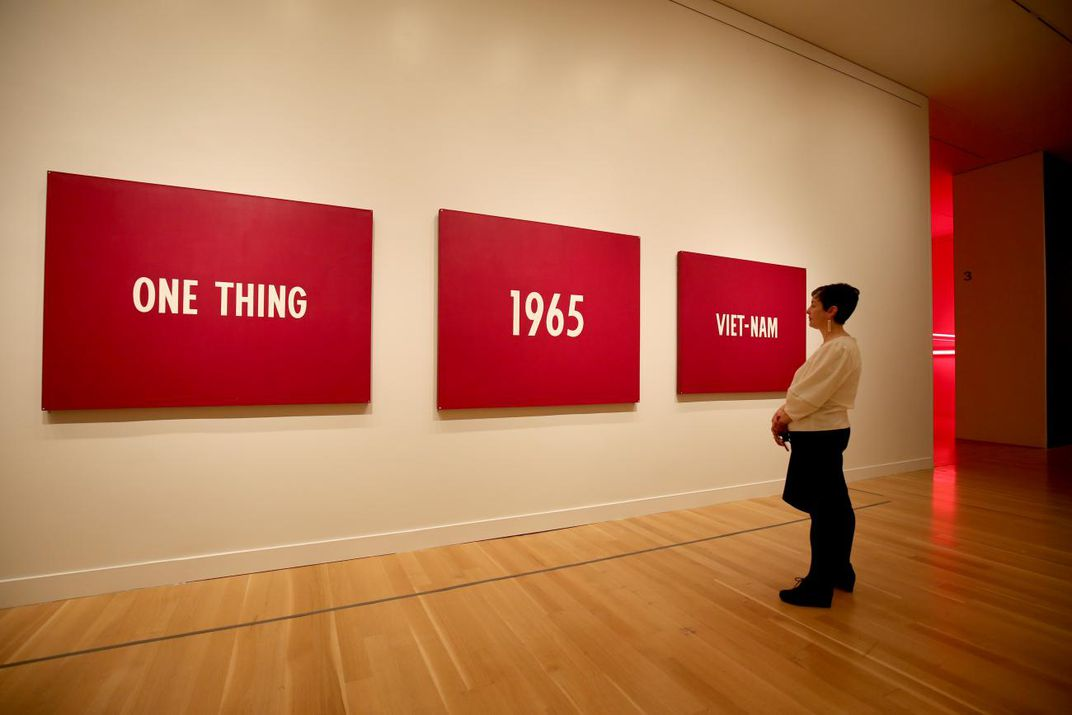 "A photograph of a woman standing in front of a three panel painting that has words that say, ""On thing, 1965, Viet-nam."""