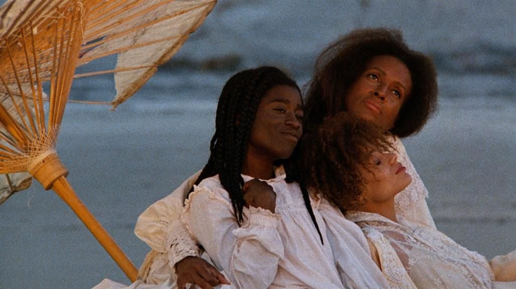A still photograph from a movie with three females sitting next to each other under an umbrella.