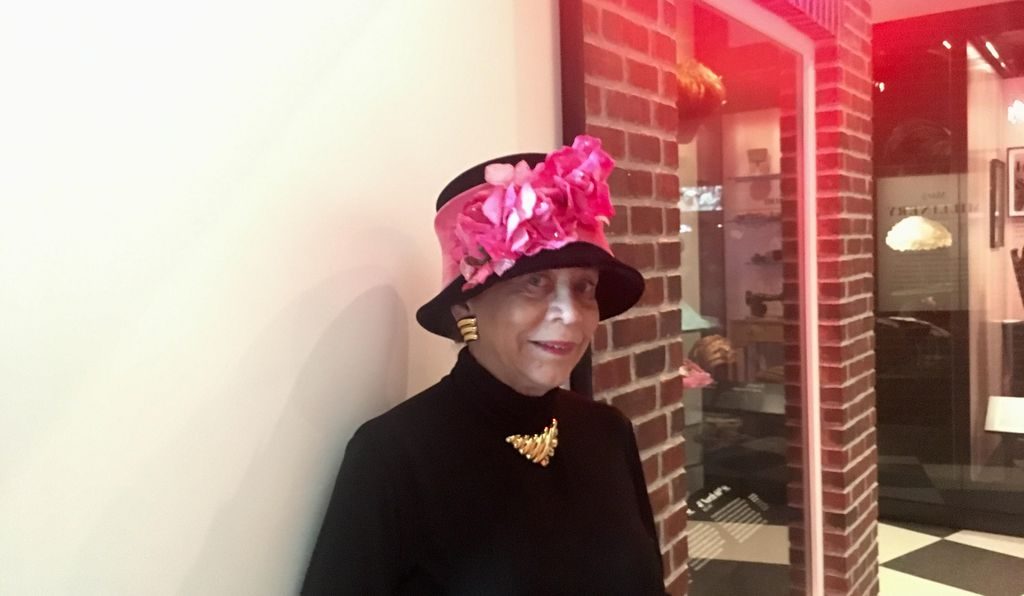 Donna Limerick wears a replica of one of her mother's hat designs while visiting the Mae's Millinery Shop exhibit at the National Museum of African American History and Culture.