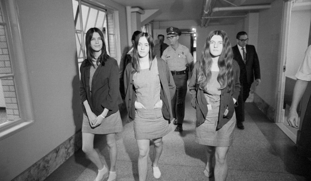 Leslie Van Houten, Susan Atkins, and Patricia Krenwinkel (left to right) walk from the jail section to the courtroom during the trial for their role in the Manson Family murders.